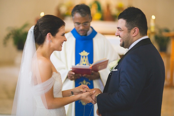 Catholic wedding ceremony in Hawaii bride places wedding ring on groom's finger priest
