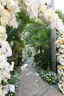 Arches of flowers along stone pathway