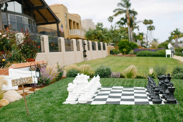Waterfront wedding with large black and white chess set on green lawn
