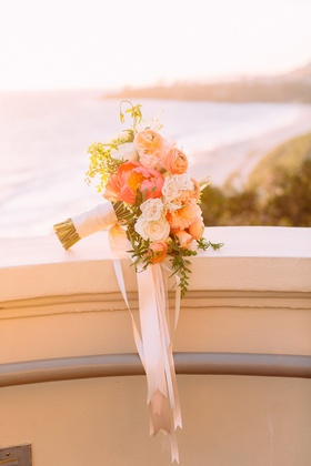 sunset photo of bridal bouquet hot pink peony white orange roses ranunculus greenery