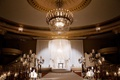 Ballroom wedding ceremony candelabra decorations white flowers candles white chuppah on stage