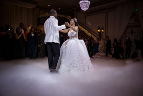 bride and groom first dance with fog machine ball gown headpiece white groom jacket chandelier