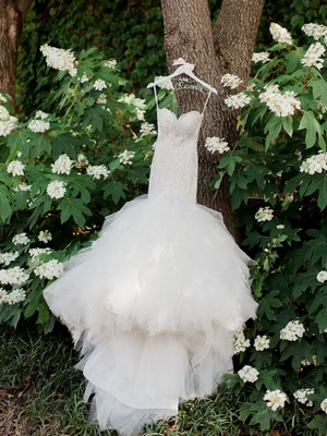 Eve of Milady wedding dress on tree trunk custom hanger tight bodice drop waist large tulle skirt