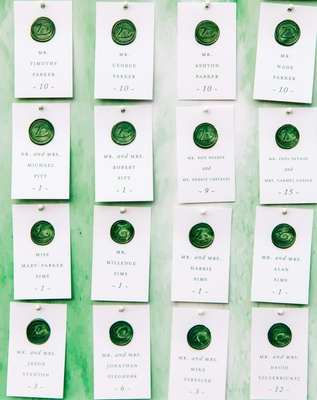 escort cards pinned to watercolor board with green swan seal wedding reception