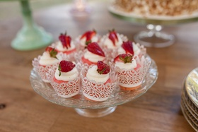 strawberry and cream treats in vintage inspired cups on glass cake tray wood table dessert table