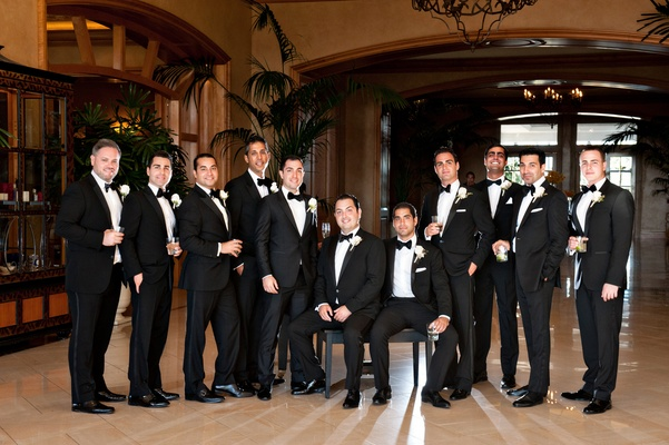 groom and groomsmen wearing black suits with black bow ties and silk accents