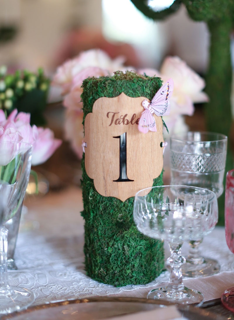Garden theme wedding with cylinder table number wrapped with moss die cut wood butterfly motif