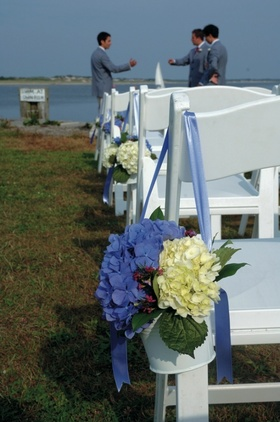 White ceremony chair with blue hydrangeas in pail