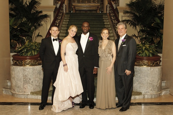Bride in a high-low Amsale gown with groom in black tuxedo and family