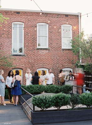 wedding event guests on washington dc rooftop gallery venue brick wall atrium glass hedge wall