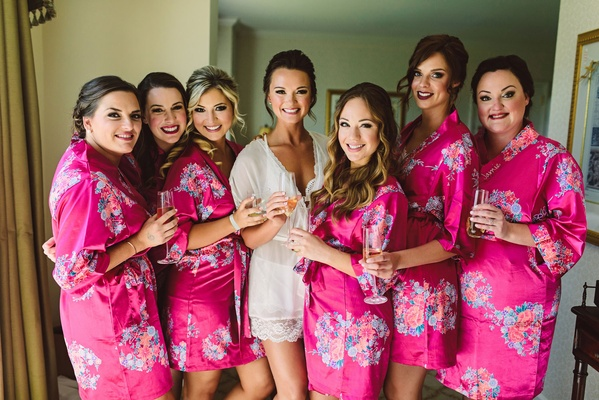 Flower print robes bright pink flower design champagne glasses bride in white robe getting ready