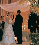 bride and groom stand under chuppah