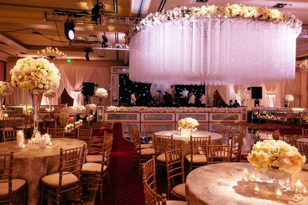 Ballroom wedding reception with high and low ivory centerpieces, dramatic crystal ceiling treatment