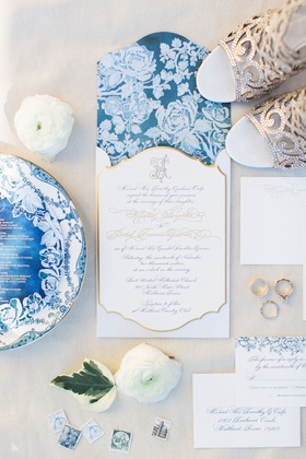 Wedding invitation with white flowers on blue background gold border calligraphy monogram