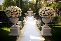 Stone pedestals filled with roses and hydrangeas