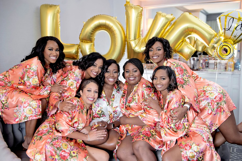 bride in white flower print robe bridesmaids in coral flower print robes gold balloons