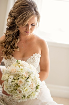 Bride in Ines Di Santo strapless wedding dress with curled hair brought to one side side bangs