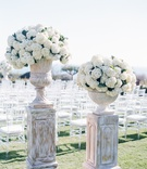 Seaside wedding ceremony with clear chiavari chairs and urns filled with white hydrangeas on stands