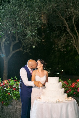 outdoor wedding cake four layer pretty traditional confection bride and groom kiss as they cut cake
