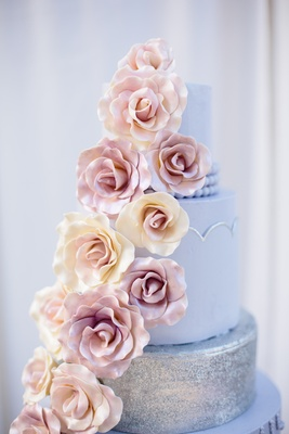 Wedding cake with lilac and silver layers and white and pink sugar roses