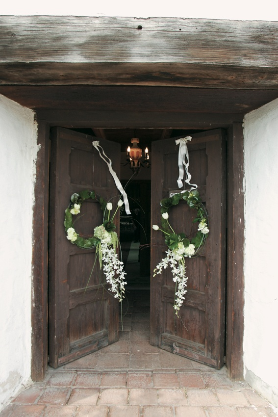 Church doors decorated with white ribbons and green wreaths with white flowers