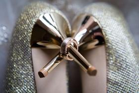 Bride's diamond wedding ring and groom's band on heel of Jimmy Choo gold shoes metallic