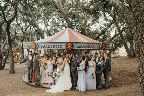 mixed gender wedding party with bride and groom on carousel at saddlerock ranch