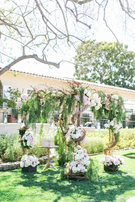 Wedding ceremony structure with birch tree, wrap-around vines, greenery, and white and pink flowers