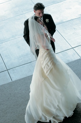Bride in a veil and wedding gown with ruching and tiered skirt