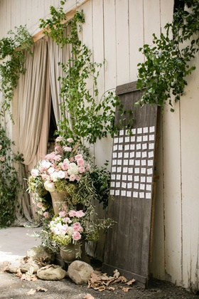 Wood board in front of barn with pink and white flowers greenery escort cards wedding reception