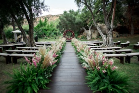 wooden aisle lined with ferns, pampas grass, and pink flowers