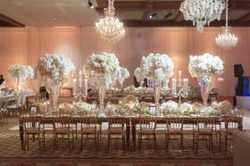 Long reception table in ballroom with tall centerpieces chandeliers mirror details candelabra