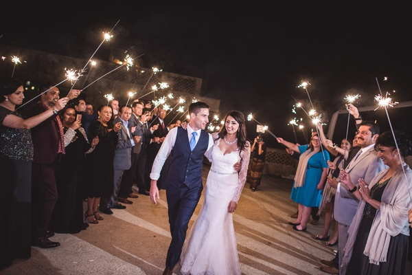 Guests create a pathway and sendoff the couple with sparklers