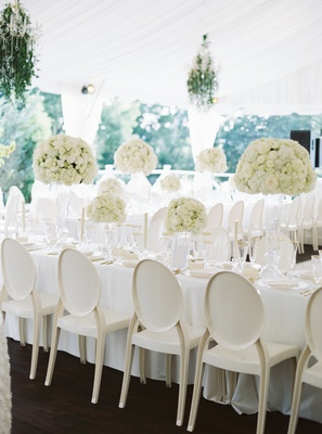 ivory round-back chairs with white linens, cream blossoms