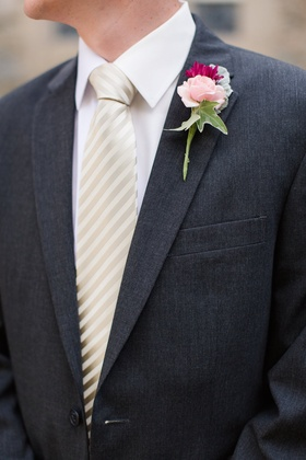 Groom in charcoal suit and striped tie with pink flower on lapel