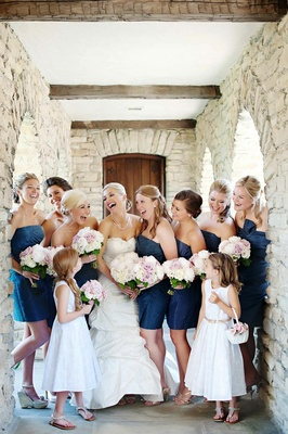 Bride with flower girls and bridesmaids in blue dresses
