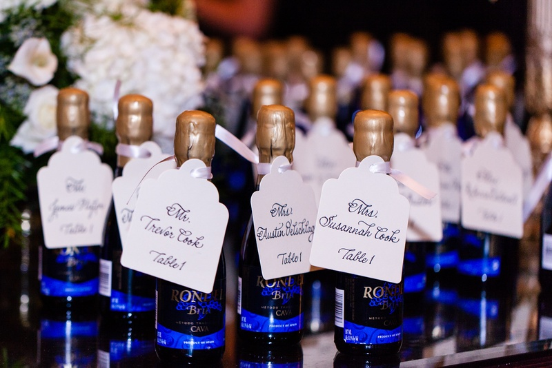 Mini blue wine bottles and gold wax with seating card tags at wedding