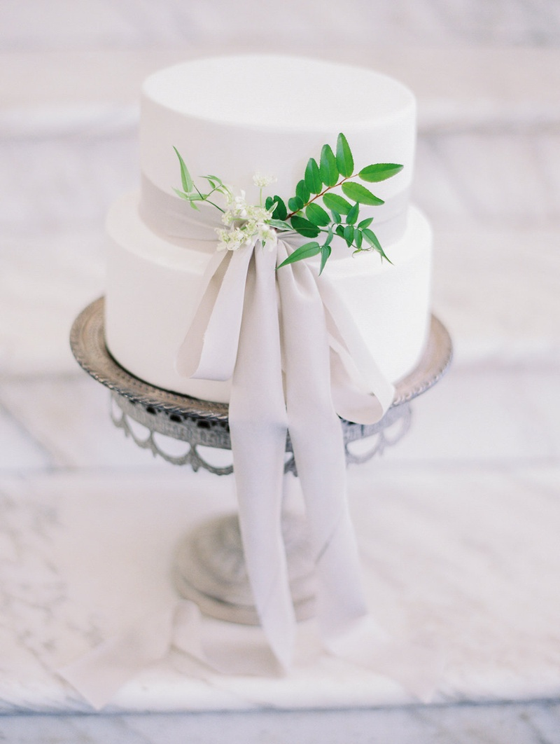 Small white wedding cake with light grey ribbon small white flowers, greenery on silver cake stand
