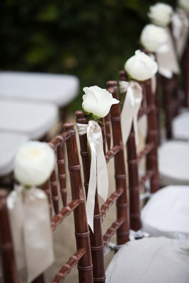 one white rose tied to each brown chair with white ribbon