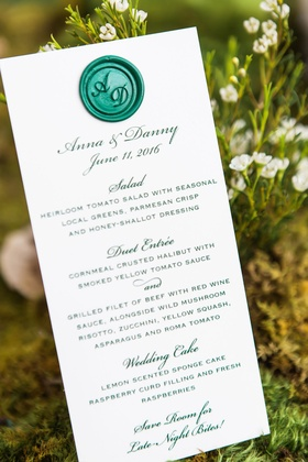 White wedding menu card with green wax seal monogram