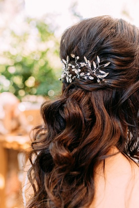 bride with long brown hair loose curls pulled back vine motif headpiece crystal details