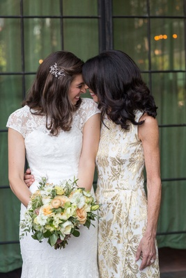 Bride in white lace cap sleeve gown from Mark Ingram Atelier with mom smiling and laughing wedding