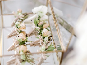 peach boutonnieres for groom and groomsmen in glass case with gold trim