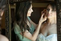 maid of honor in green bridesmaid dress helps bride with earrings