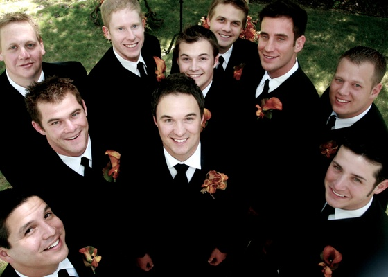 Groom and groomsmen in black tuxedos and orange boutonnieres