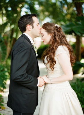 groom holding brides hand kiss on forehead florida wedding beaded bridal gown black suit half up