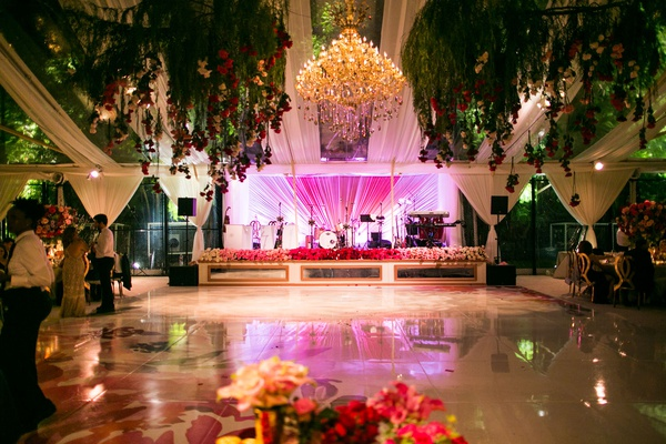 wedding reception watercolor dance floor pink lighting chandelier live band stage greenery ceiling