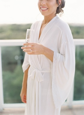 Bride in white robe with engagement ring holding champagne flute with gold calligraphy
