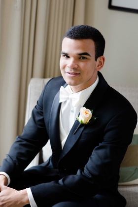 groom in nice black suit tuxedo with white bow tie and rose boutonniere peach pink