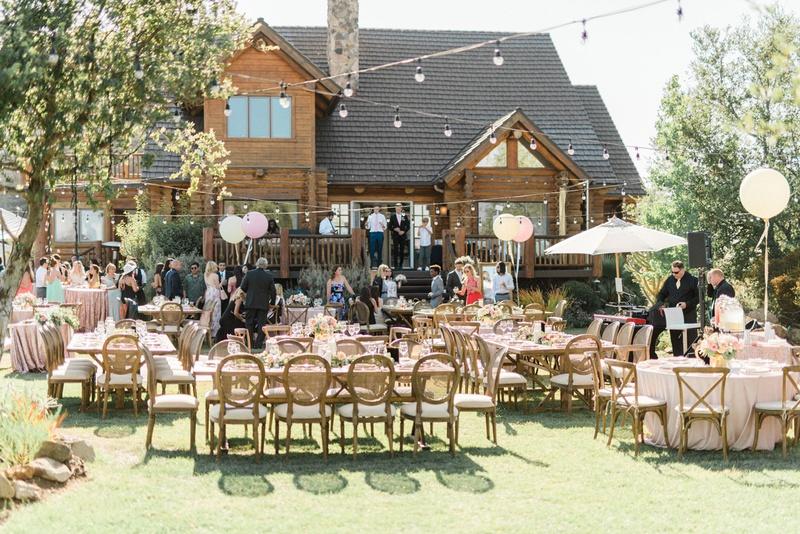 Outdoor wedding reception malibu estate venue backyard wedding balloons umbrellas pink wood greenery